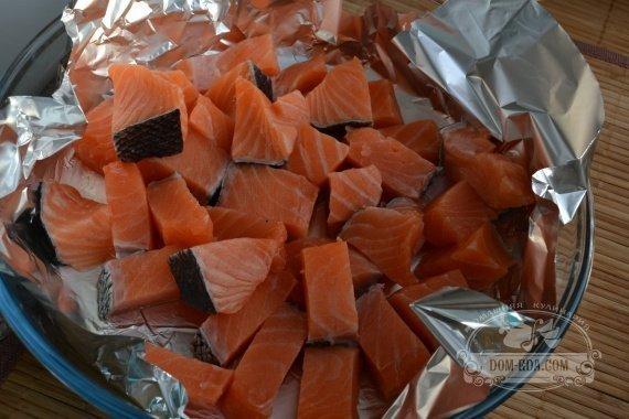 Раскладываем кусочки рыбы на фольгу.